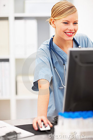 Portrait of smiling lady doctor using the computer