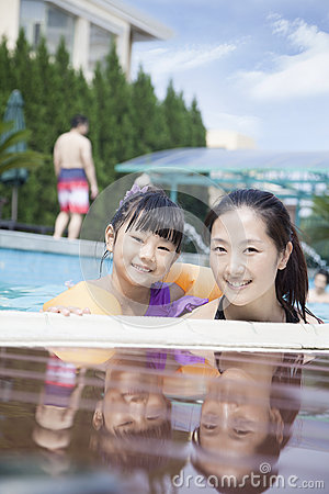 Portrait of smiling mother and daughter in the pool by the edge looking at camera