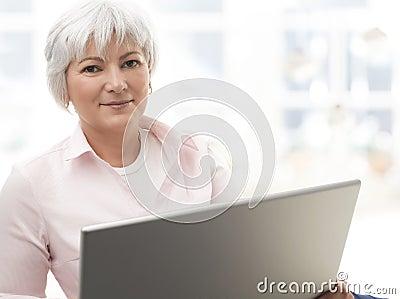Smiling senior woman working on laptop