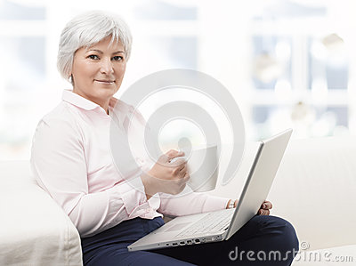 Smiling senior woman working on laptop