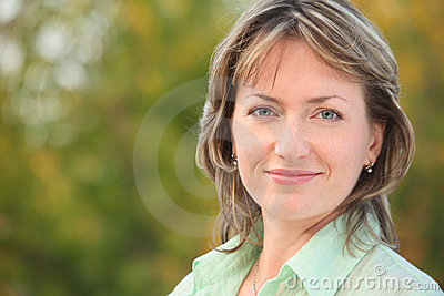 Portrait of smiling woman in early fall park Stock Photo