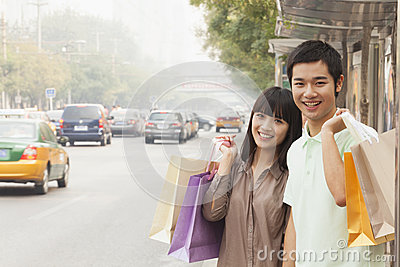 Portrait of smiling young couple carrying colorful shopping bags and waiting for the bus at the bus stop, Beijing, China