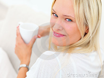 Portrait of a smiling young lady drinking coffee