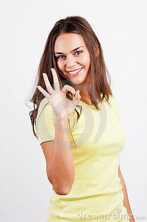 Portrait of smiling young woman gesturing okay
