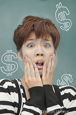 Portrait of stressed young woman with money problems, in front of blackboard with money signs