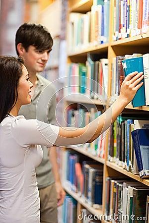 Portrait of students choosing a book on a shelf