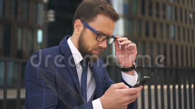 Portrait of successful businessman is using smartphone on background of city building. Portrait of successful businessman is using smartphone on background of stock video