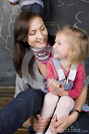 Portrait of teacher and little student, mother and daughter near blackboard