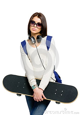 Portrait of teenager with skateboard, headphones and rucksack