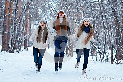Portrait of three beautiful girls in winter park