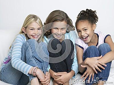 Portrait Of Three Friends Hugging Knees