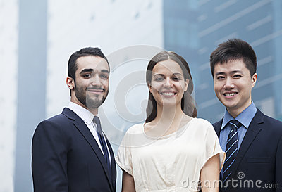 Portrait of three smiling business people, outdoors, business district