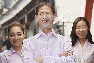 Portrait of three smiling well-dressed people standing in a row, Beijing