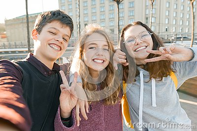 Portrait of three teen friends boy and two girls smiling and taking a selfie outdoors. City background, golden hour Stock Photo