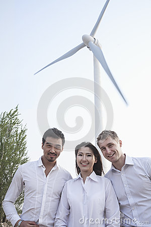 Portrait of three young business people standing in front of a wind turbine, looking at camera