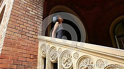 Portrait tiré de la belle jeune femme dans le chapeau dans la vieille ville outdoors banque de vidéos