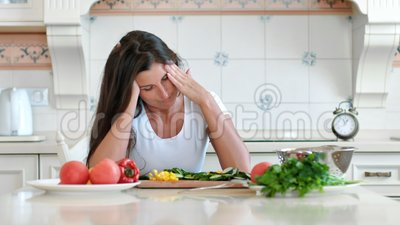 Portrait tired female housewife having headache touching head making circular massage while cooking. Portrait of tired female housewife having headache touching stock footage