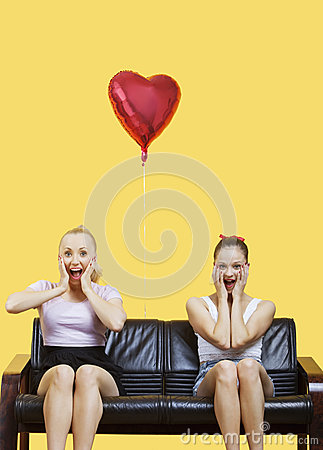 Portrait of two amazed young women sitting on sofa with heart shaped balloon over yellow background