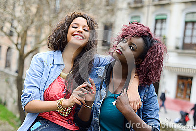 Two beautiful girls in urban backgrund, black and mixed women