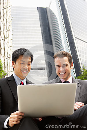 Portrait Of Two Businessmen Working On Laptop