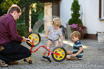 Portrait of two cute boys repairing bicycle wheel with father ou