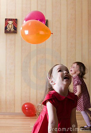Portrait of two little girls playing with balls