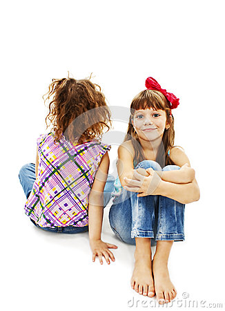 Portrait of two little girls sitting back to back and smiling