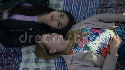 Diverse cute girls resting on park lawn in spring stock footage