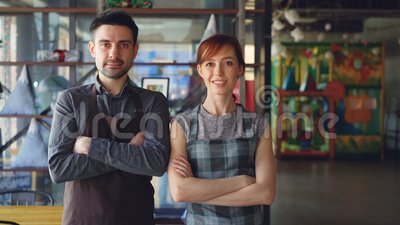 Portrait of two proud small business owners standing inside new spacious cafe and smiling. Successful business start-up. Portrait of two proud small business stock video