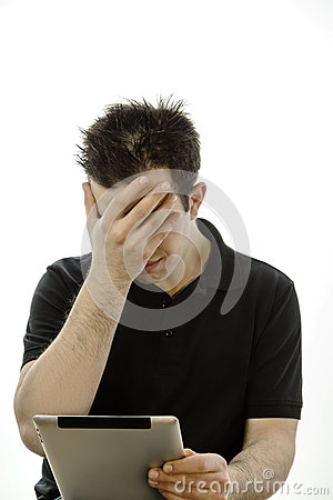 Portrait of a unhappy young man with tablet pc