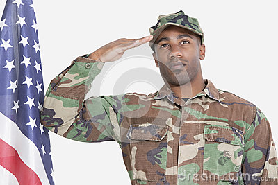 Portrait of US Marine Corps soldier saluting American flag over gray background
