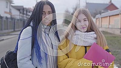 Portrait von zwei schönen Mädchen, die Kamera anschauen und lächeln kaukasisch-afrikanisch-amerikanische Teens im Freien stock video