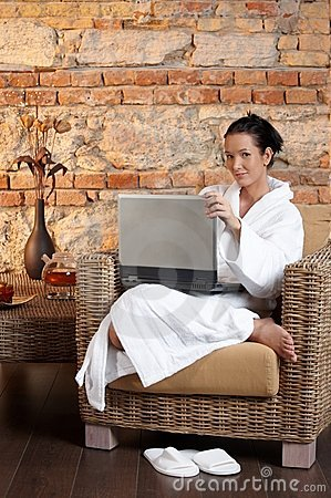 Portrait of woman in bathrobe with laptop