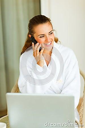 Portrait of woman in bathrobe speaking mobile