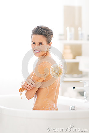 Portrait of  woman with body brush in bathtub