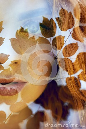 Portrait of a woman with a double exposure, the girl and the blurred nature of the photo is not in focus. The leaves on the woman. Stock Photo
