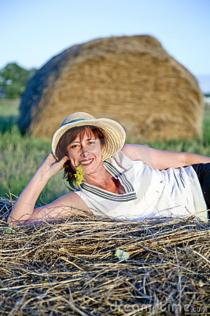 Portrait of woman lying on a haystack