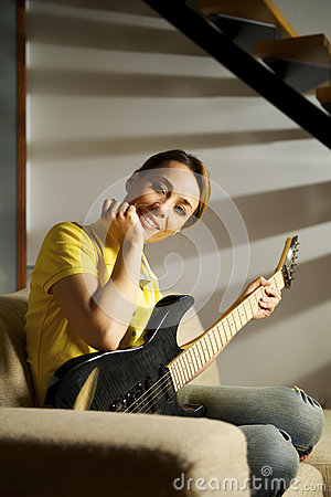 Portrait of woman playing with electric guitar at home