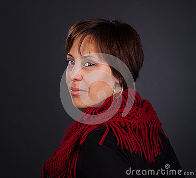 Portrait of a woman in red scarf looking back. Close-up portrait