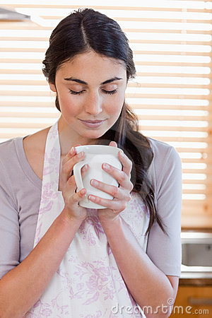 Portrait of a woman smelling a cup of coffee