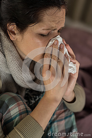 Portrait of woman sneezing into tissue