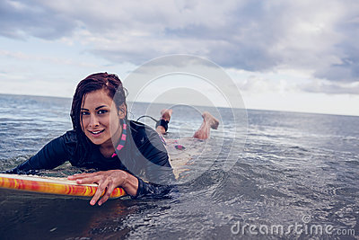 Portrait of a woman swimming over surfboard in water