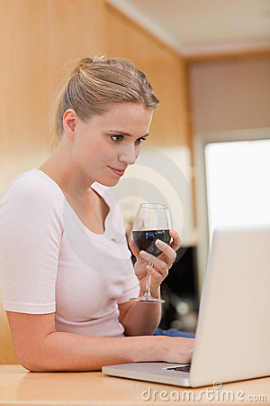 Portrait of a woman using a laptop while drinking wine