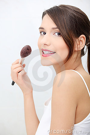 Portrait of young adult woman applying blusher