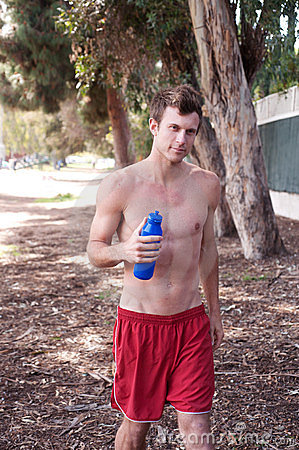 Portrait of a young athletic runner with water bot