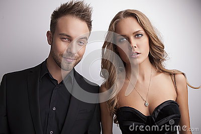 Portrait of young attractive couple posing at studio dressed in black fashionable clothes.