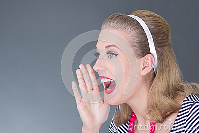 Young attractive pinup girl in striped dress screaming