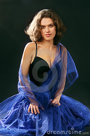 Portrait of young attractive woman in blue dress