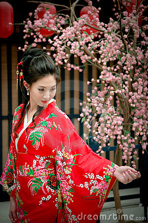Portrait of young beautiful girl in red kimono