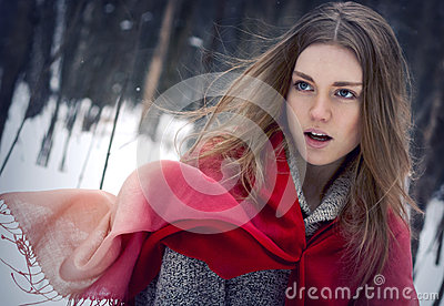 Portrait of the young beautiful girl with red scarf in the winte
